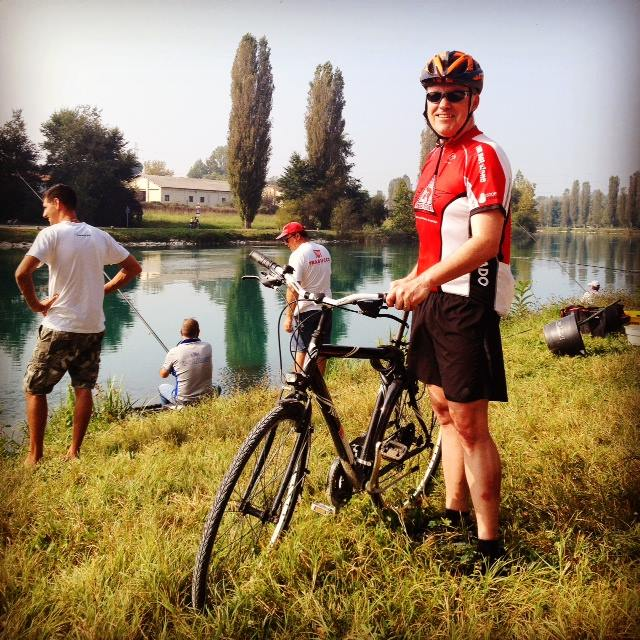 With Italian fisherman and cypress trees in the background, I pose for my official Tour de Cure photo in Italy.